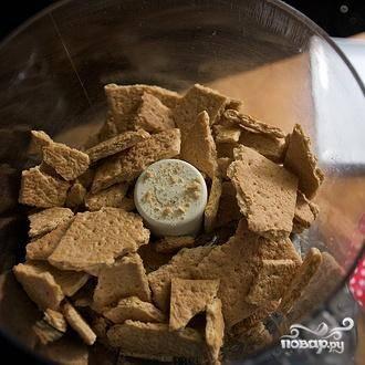 2. В кухонном комбайне перемешать крекеры с 2 столовыми ложками сахара. Добавить сливочное масло и перемешать, пока смесь не будет напоминать мокрые крошки.