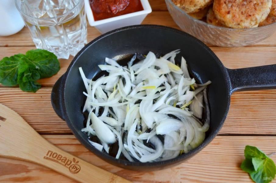 Вторую луковицу порежьте полукольцами и обжарьте на двух столовых ложках масла со щепоткой соли.