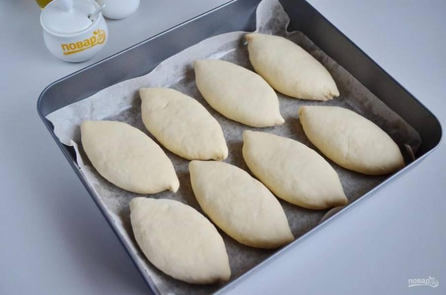 9. Застелите противень бумагой, смажьте ее масло растительным. Уложите пирожки швом вниз на небольшом расстоянии друг от друга. Дайте им подойти в тепле минут 20. Потом смажьте взбитым яйцом и выпекайте при 180 градусах минут 30.