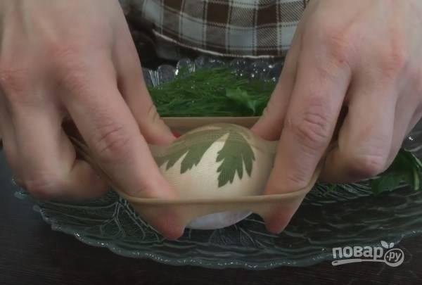 2. Разрежьте носочек на 2 части. Растяните половинку и наденьте на яйцо.
