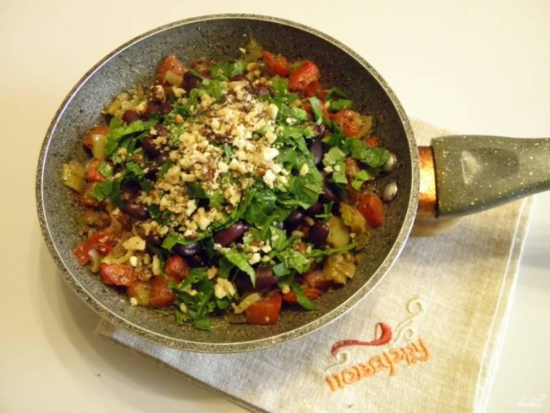 Фасоль отцедите от жидкости, добавьте на сковороду к овощам, туда же — орехи и мелко порезанную зелень. Перемешайте и протушите пару минут на сковороде.