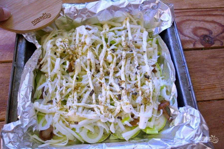 Натрите на терке твердый сыр. Сыр выложите на овощи. Полейте немного майонезом и посыпьте специями. У меня специи к грибным блюдам с небольшими кусочками сушеных лесных грибов.