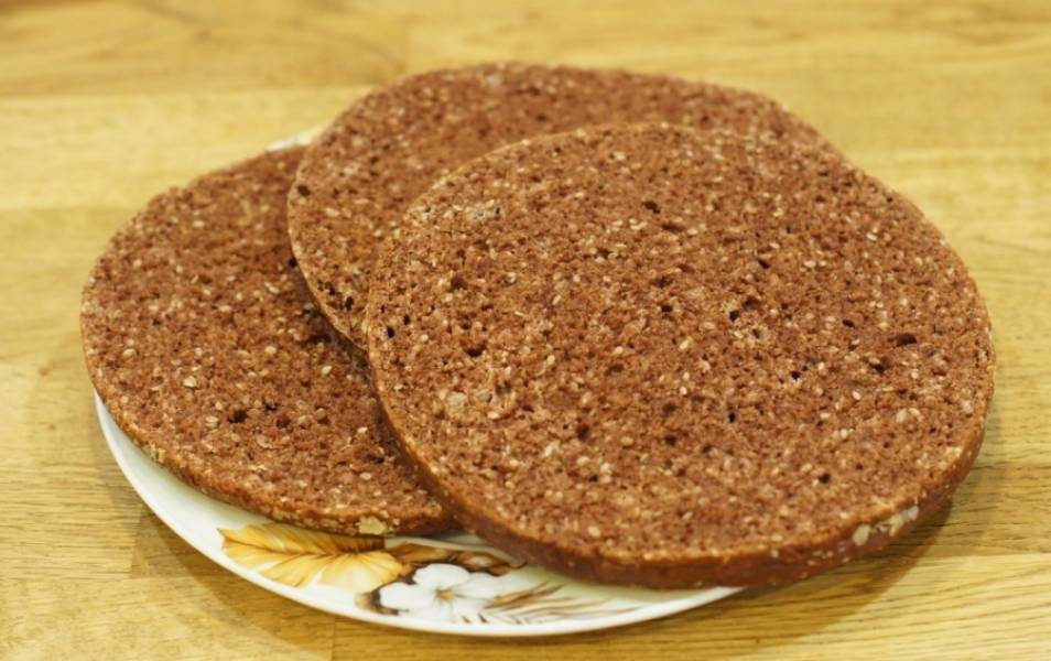 Разрезаем его на три коржа. Для крема смешиваем: сметану, 2 ч.л. ванильного сахара и 60 грамм сахара.