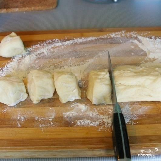 Из поднявшегося теста раскатываем колбаску, которую нарезаем на кусочки шириной около 3 см.
