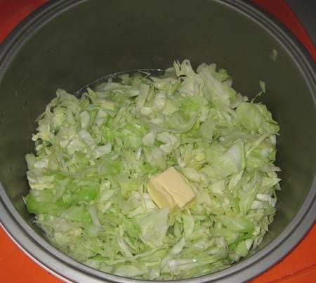 2. Нашинковать капусту и выложить в сковороду с толстым дном. Добавить сливочное масло и тушить на среднем огне до мягкости.