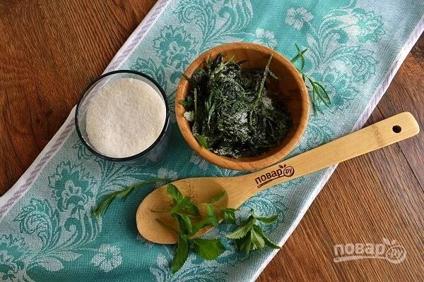 Листья мяты и тархуна засыпьте 1 с.л. сахара и разомните толкушкой.