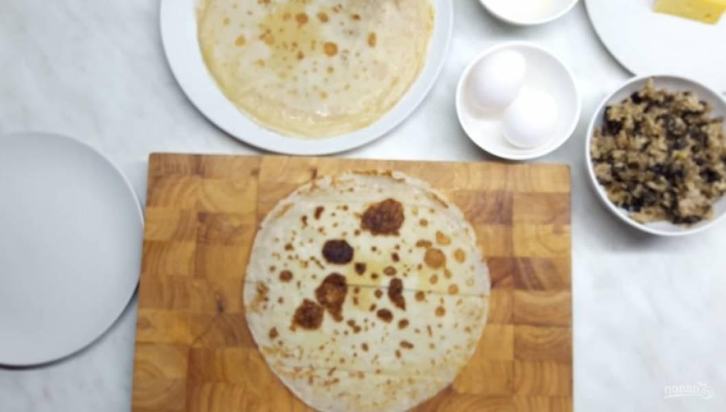 1. Для начала приготовьте начинку: обжарьте шампиньоны с луком и курицей. Далее подготовьте блины: разрежьте их на на две части.