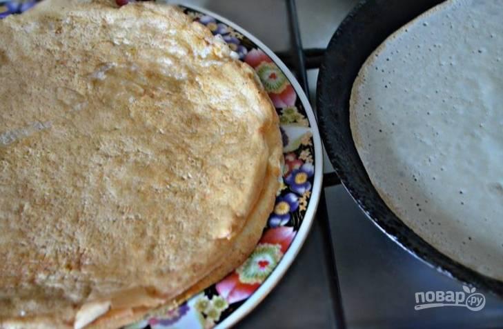 4.С помощью кисточки смажьте сковороду растительным маслом и вылейте примерно 0,5 стакана теста, обжаривайте блины с двух сторон до золотистой корочки.
