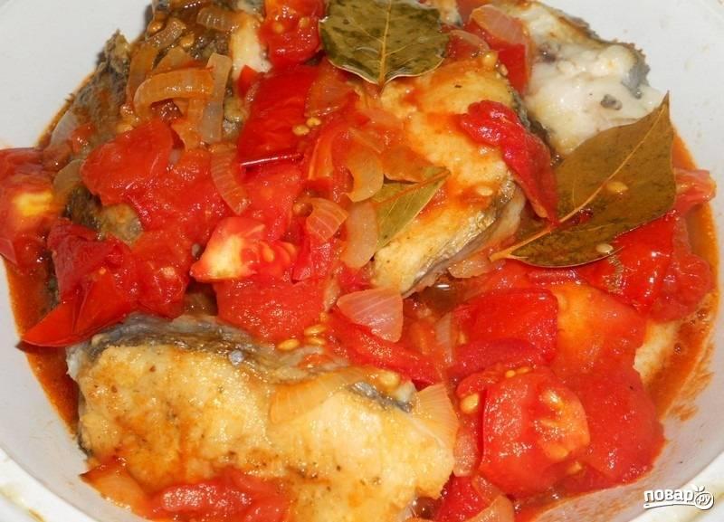 3.На этой же сковороде обжариваю предварительно почищенный лук и помидор. Томатную пасту развожу в небольшом количестве воды и заливаю овощи, солю и перчу, тушу до образования густой массы (как соус). Заливаю полученной массой рыбу, кладу лавровый лист и готовлю 15 минут.