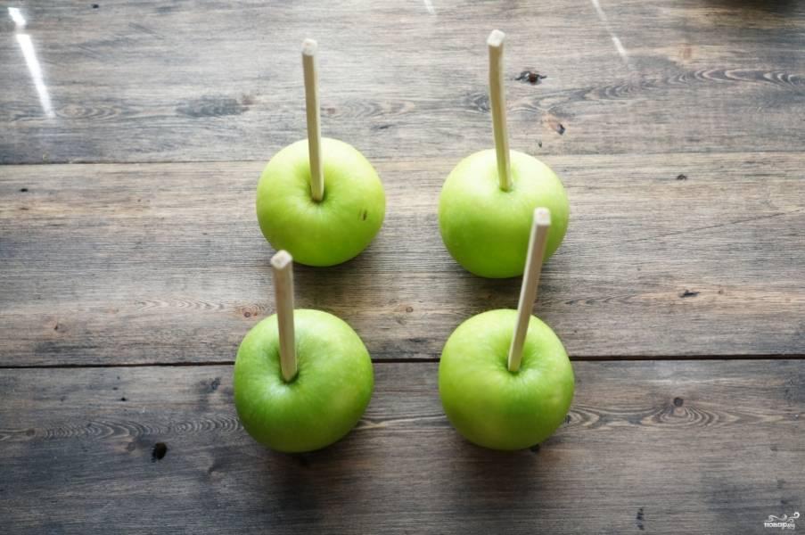 """Яблоки вымойте и вытрите насухо бумажным полотенцем. Проткните их палочками. Можно использовать одноразовые для китайской еды. Сорт яблок выбирайте на свое усмотрение, лучше, если они будут кисло-сладкими. К примеру, подойдет сорт """"Гренни Смит""""."""
