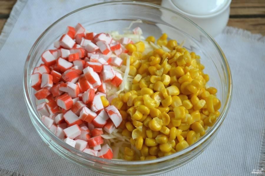 Добавьте к капусте кукурузу и крабовые палочки.