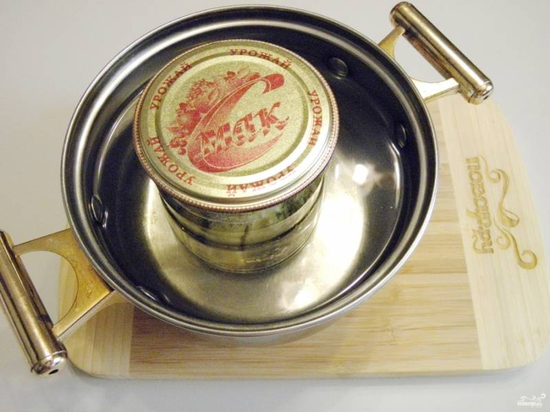 Плотно утрамбуйте огурчики по баночкам и залейте соком со специями. Накройте стерильными крышками, стерилизуйте баночки (по 30 минут каждую). После закатайте и храните в прохладном месте.