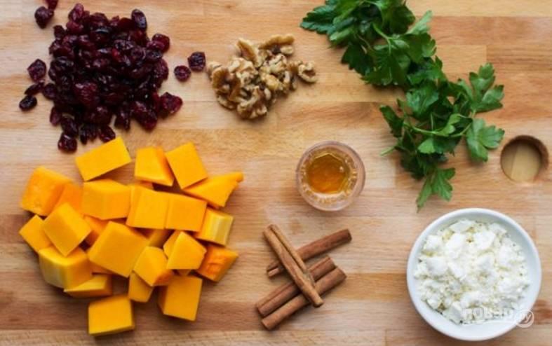 Подготовьте продукты: тыкву порежьте некрупным кубиком, орехи подробите, сыр покрошите, петрушку измельчите.
