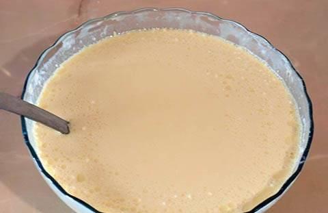 3. Всыпать муку, постоянно помешивая. Влить тонкой струйкой молоко (можно заменить водой при желании). Тесто должно получится довольно жидким. Добавить пару ложек растительного масла и еще раз перемешать.