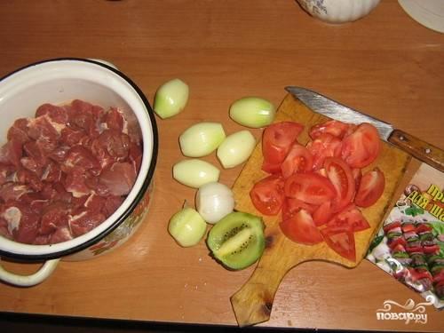 Подготавливаем мясо - отделяем пленки и режем на кусочки вашего любимого размера, но не очень крупные. Чистим и режем лук, моем помидоры и разрезаем на дольки. Киви очищаем и нарезаем не очень мелко.