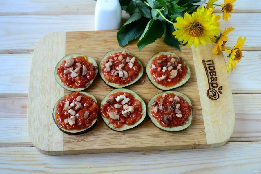 Каждый кружок баклажана смажьте томатным соусом. Шампиньон мелко порежьте и выложите кусочки сверху на соус.