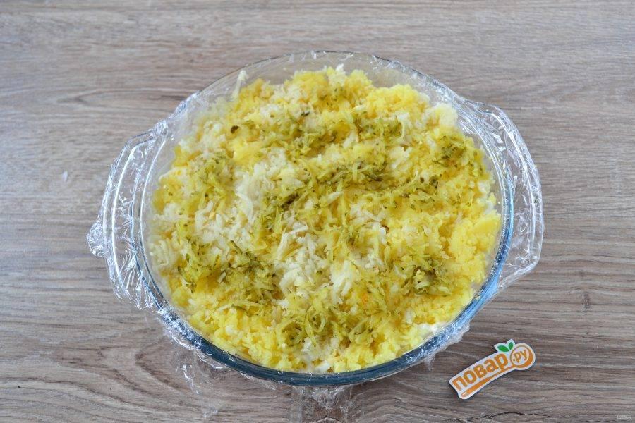 Картофель натрите на мелкой терке, на такой же терке натрите соленые огурцы. Выложите их последними слоями и смажьте майонезом.
