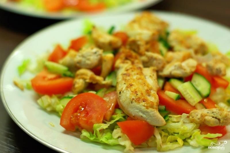 На тарелочку выкладываем овощи, сверху кладем кусочки курицы.