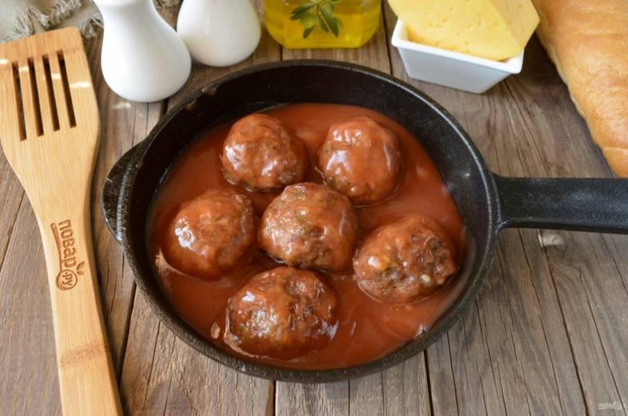 На сковороде разогрейте томатный соус, как только он дойдет до кипения, поместите в него готовые фрикадельки и обваляйте со всех сторон, протушивая в соусе пару минут.