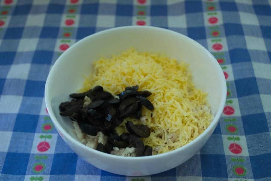 2. Отварные яйца натрите на терке. Натрите на терке сыр. Соедините мясо птицы, сыр, яйца. Добавьте нарезанные маслины.
