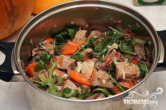 4. Мясо смешиваем с помидорами, квашеной капустой и порезанным перцем. Добавляем сливочного масла. Перемешиваем, добавляем кедровые орехи и рукколу. Все укладываем в тыкву.