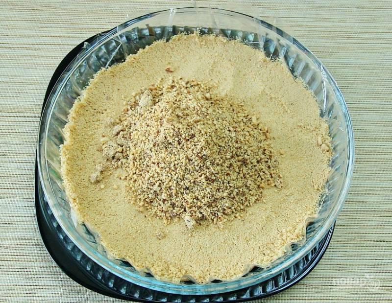 На дно формы для выпечки выложите крошки печенья и миндаль.