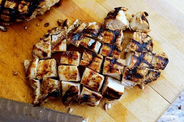 Разрежьте обжаренное на гриле куриное филе на маленькие одинаковые кусочки.