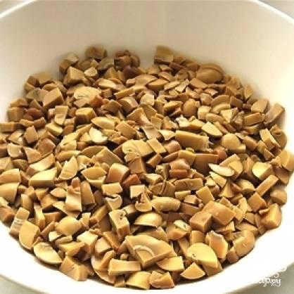 Укладываем в салатницу мелко нарезанные маринованные грибы.