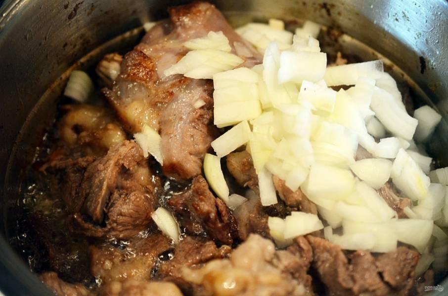 8. К мясу добавляем нарезанный лук. Обжариваем минут 10.