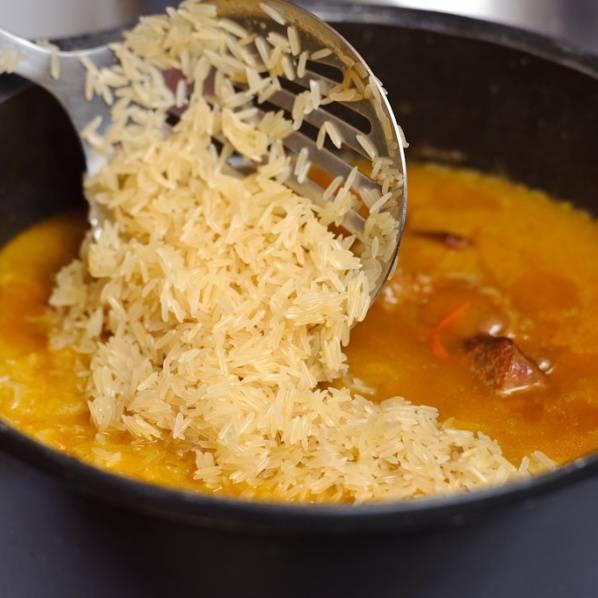 По истечении 1 часа удалите чеснок и добавьте рис в чугунок. Добавьте еще немного воды если потребуется.
