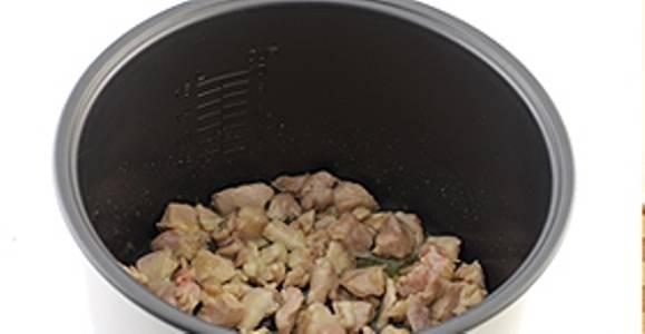 """Выберите режим """"Выпечка"""". В мультиварку налейте растительное масло и выложите порезанное мясо. Обжаривайте курицу 15-20 минут с открытой крышкой."""