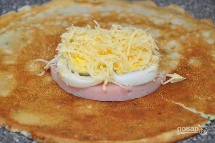 На каждый блин выкладываем: ломтик ветчины, несколько кружочков порезанных сваренных яиц и тертый сыр.