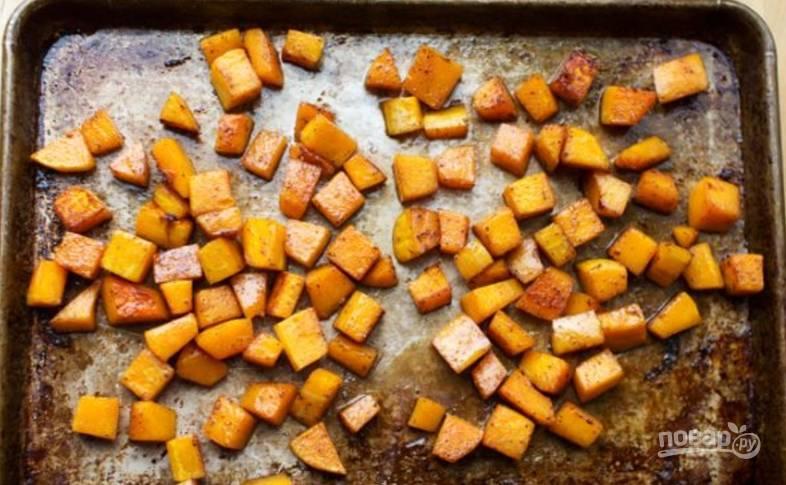 Прогрейте духовку при 200 градусах. Смешайте кусочки тыквы с маслом, медом, солью, перцем и корицей. Тыква должна покрыться заправкой. Выложите овощ на противень в один слой.