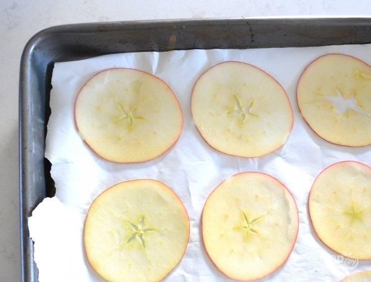 1.Вымойте яблоки, нарежьте их тонкими кружочками (воспользуйтесь теркой или ножом). Застелите противень пергаментом, выложите яблочные кружочки.