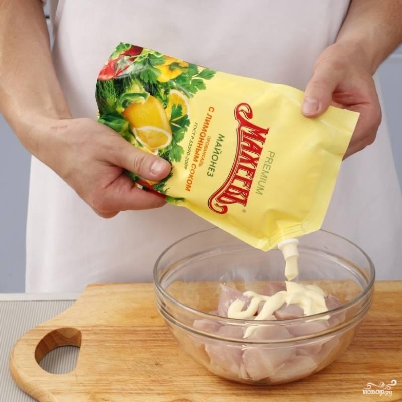 Куриное филе нарезаем на кубики стороной 4 см, кладем в миску, добавляем майонез, соль и перец. Перемешиваем и оставляем мариноваться на полчаса.