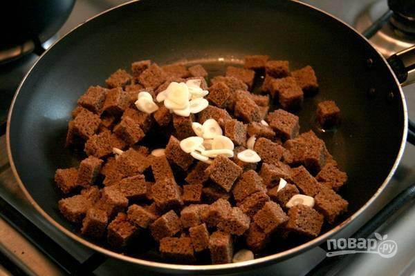 1.Черный хлеб у меня вчерашний, нарезаю его небольшими кубиками и обжариваю на сковороде с добавлением растительного масла. Очищаю и нарезаю чеснок тонкими пластинками, добавляю в самом конце к сухарикам.