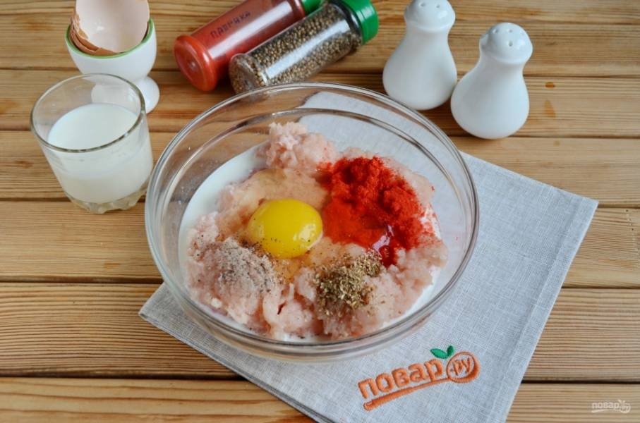 Добавьте сырое яйцо, паприку, перец черный молотый,  молотый кориандр, соль, молоко. Перемешайте тщательно.