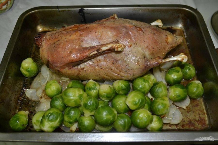 Когда утка почти готова и приобрела красивый золотистый цвет, добавьте заранее отваренную брюссельскую капусту, поставьте заново запекаться на 15-20 минут. Готовое мясо порежьте на куски и подавайте к столу.