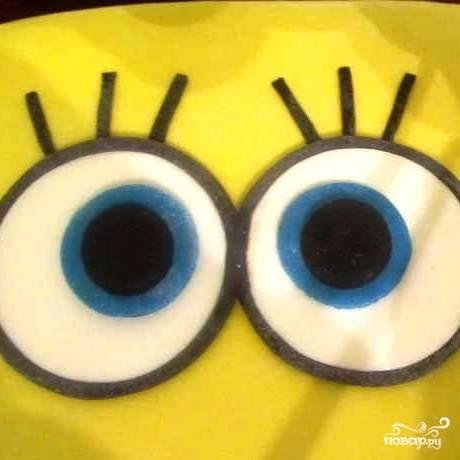 При помощи этой самой черной колбаски обводим глаза Спанч Боба. Из голубой мастики делаем зрачок, его тоже обводим черной мастикой. Внутрь голубого зрачка вставляем кружок из черной мастики. Таким образом, сделаем глаза Спанч Боба.