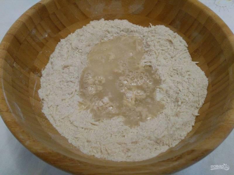 Сделав углубление в полученной массе, влейте тёплую (температура — 30-35 градусов) воду и замесите тесто. Оно получается довольно плотным.