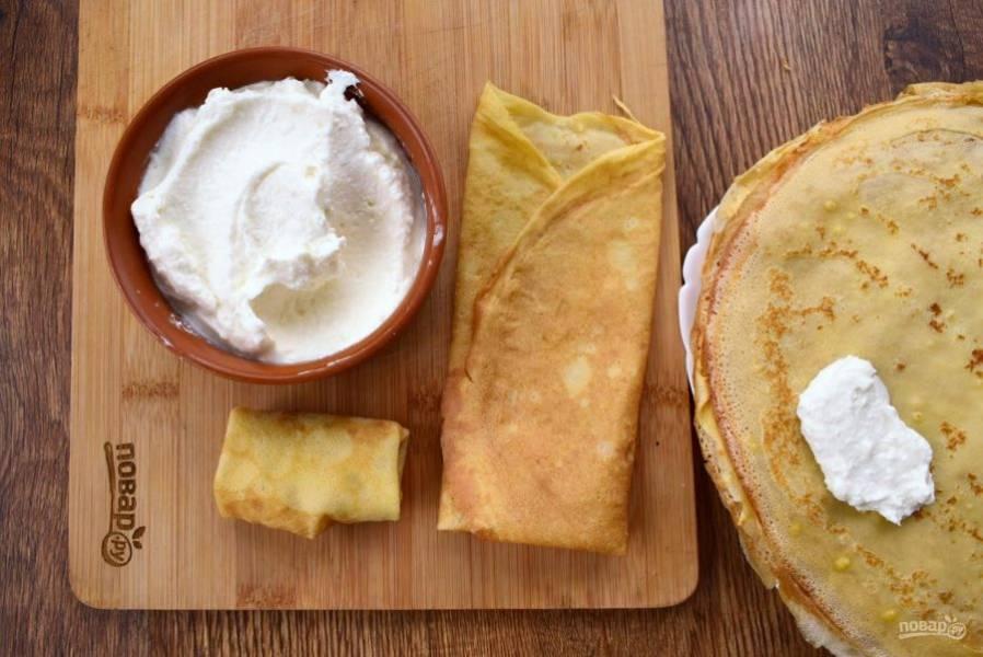 2.    Творог соедините с яйцом, сахарной пудрой и ванилином, пробейте с помощью блендера до состояния крема. Начинку выкладывайте на край блина по столовой ложке. Заверните блин конвертиком.