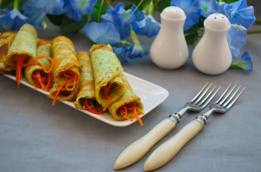 Подайте красивые блинчики к столу. Контраст зеленых блинчиков и оранжевой морковки делает блюдо праздничным и интересным.