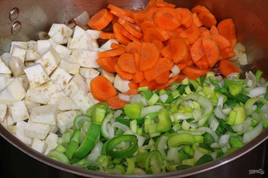 4.Очистите корень сельдерея и нарежьте его небольшими кубиками. Нарежьте кружочками или полукольцами морковь и лук-порей. Выложите овощи в кастрюлю, перемешайте и готовьте 4-5 минут.