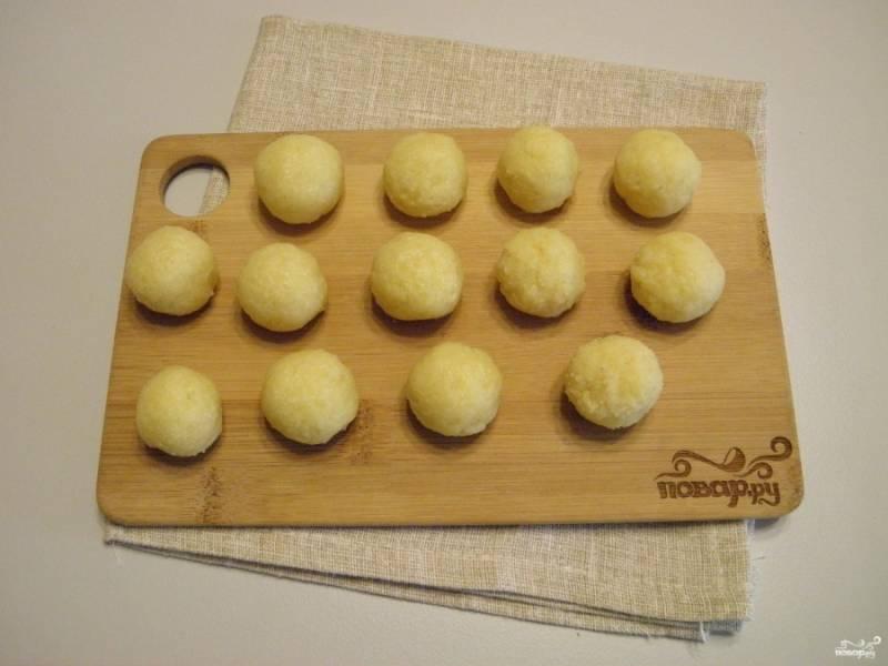 Слегка влажными руками набирайте по чайной ложке картофельной массы, катайте шарики. Величина шарика должна быть с грецкий орех или вишенку.