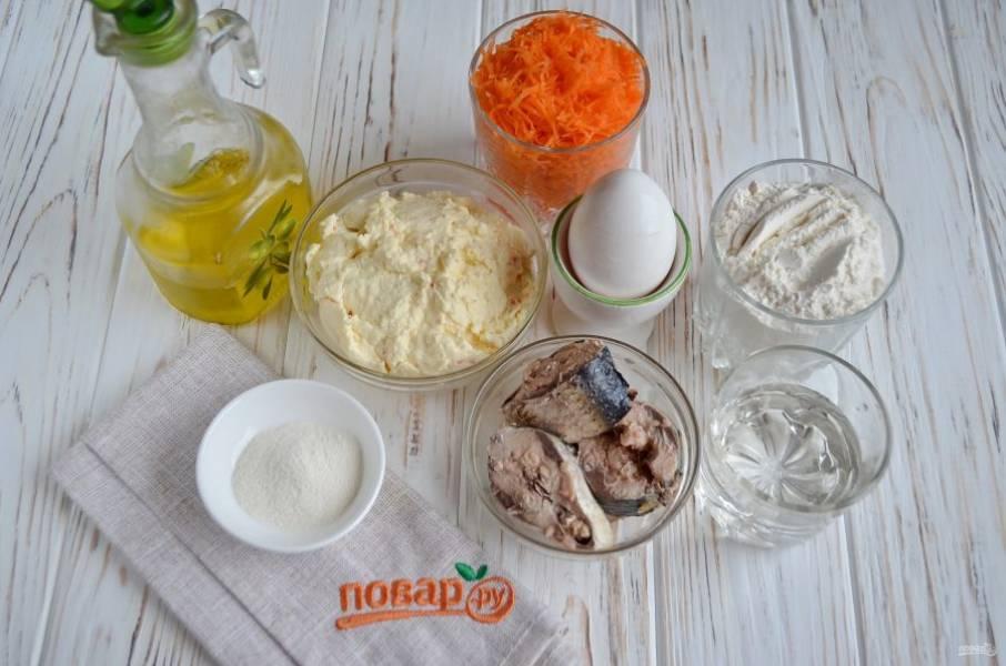 Подготовьте продукты для торта. Откройте консерву, отцедите рыбу от жидкости. Морковь очистите и натрите на мелкой терке. Сливочный сыр взбейте миксером.