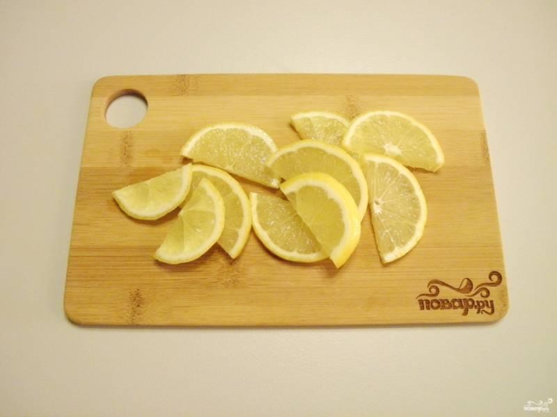 Половинку лимона порежьте дольками. Вторую половинку оставьте пока.