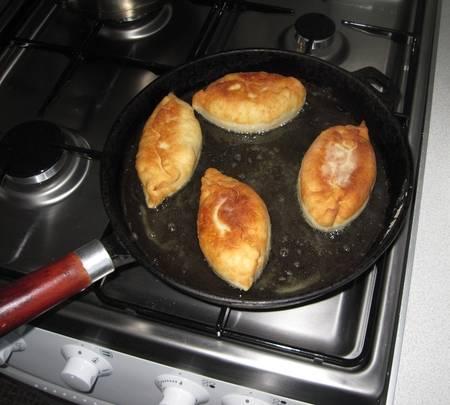 6. На сковороде разогреть растительное масло. Жарить пирожки на среднем огне до золотистой корочки. Когда капустные пирожки жареные в домашних условиях готовы, выложить на бумажное полотенце, промокнуть масло и можно пробовать.