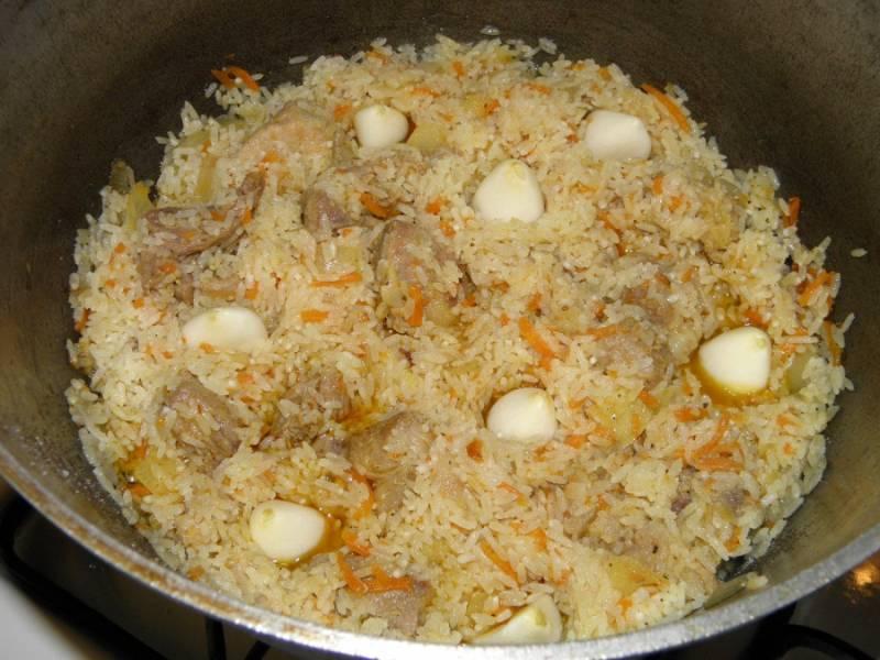 9. Добавьте рис, перемешайте, как бы обжаривая рис в жиру. Вставьте внутрь чеснок.