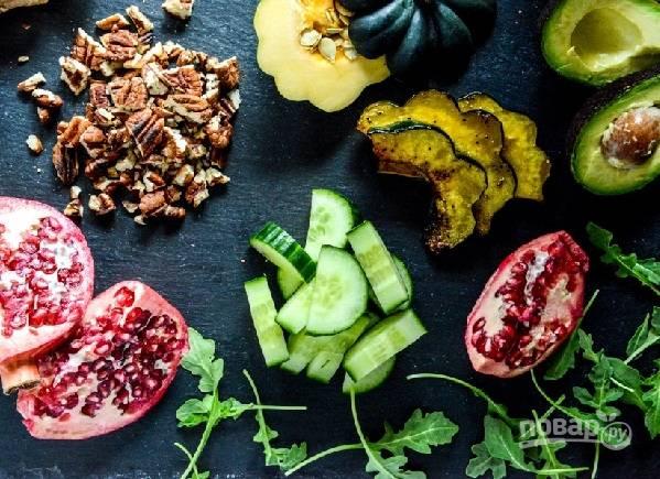 3. Вымойте и обсушите рукколу. Нарежете небольшими кусочками огурчик и тонкими ломтиками авокадо. Орешки тоже слегка измельчите ножом.