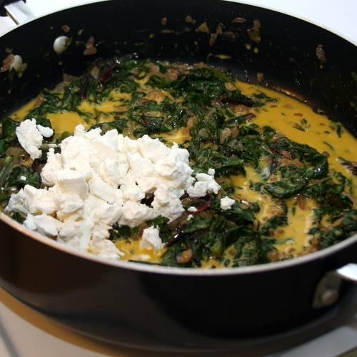 2. Когда зелень уменьшится в объеме, добавим сыр и специи по вкусу. Перемешаем, и на маленьком огне доводим до кипения, после чего снимаем с огня.